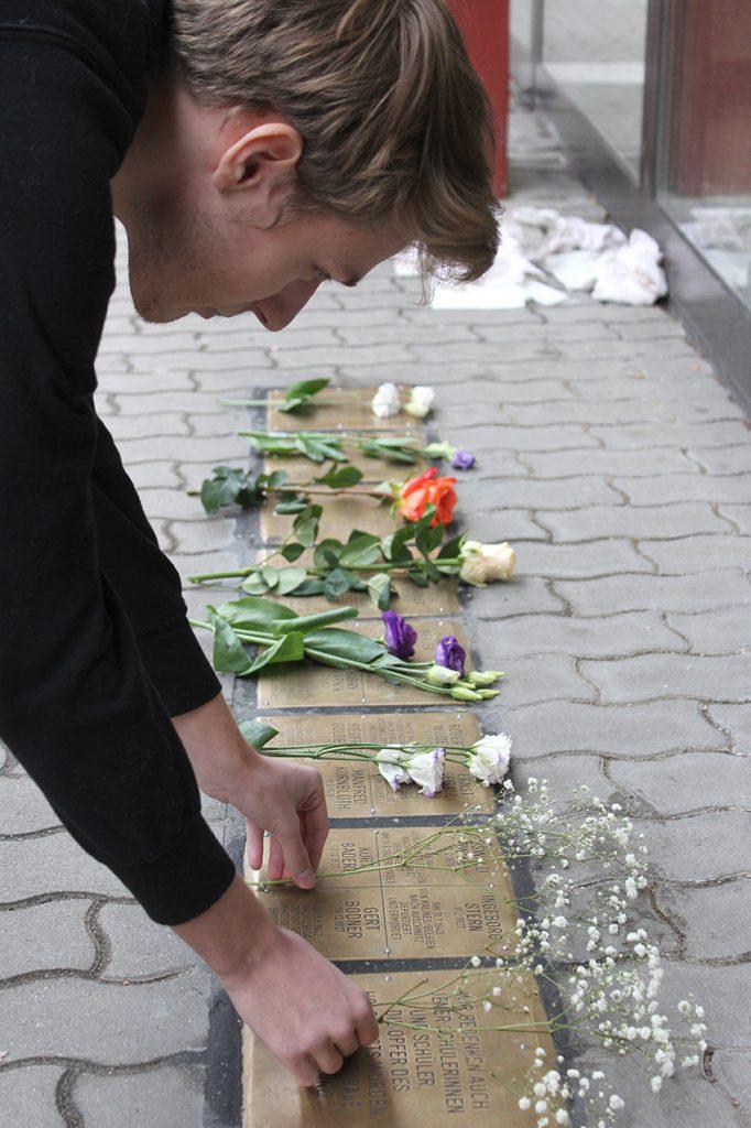 Schüler legt Blumen nieder